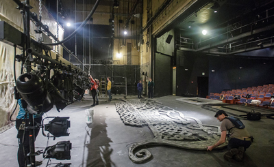 Students building a theatrical set on stage